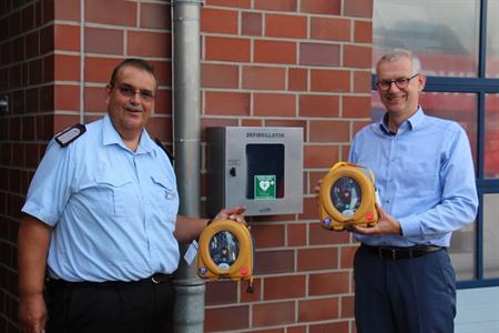 Stefan Standke, Ausbildungsleiter der Uelzener Kreisfeuerwehr (l.), und Landrat Dr. Heiko Blume präsentieren die neuen Defibrillatoren, die Betroffene vor dem plötzlichen Herztod bewahren können